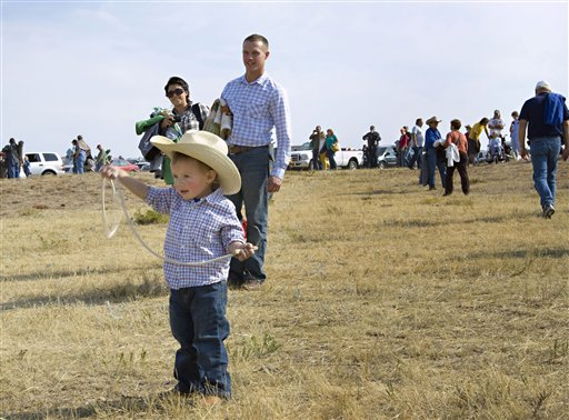 Two-year-old Jameson Maxwell plays cowboy as parents Maria and Ryan Maxwell of Rock Valley, Iowa, look on, Monday, Sept. 24, 2012 in Custer, S.D. The family was among more than 14,000 spectators from across the world who gathered to watch the herding of about 1,000 buffalo during the 47th annual Buffalo Roundup in western South Dakota's Custer State Park.